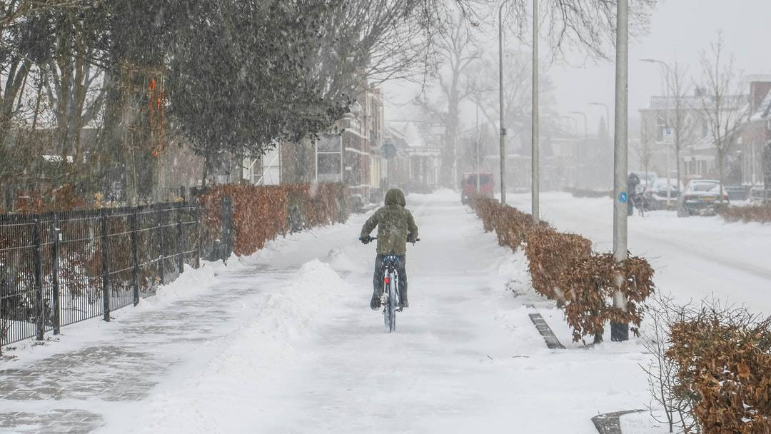A person riding skis down a snow covered street