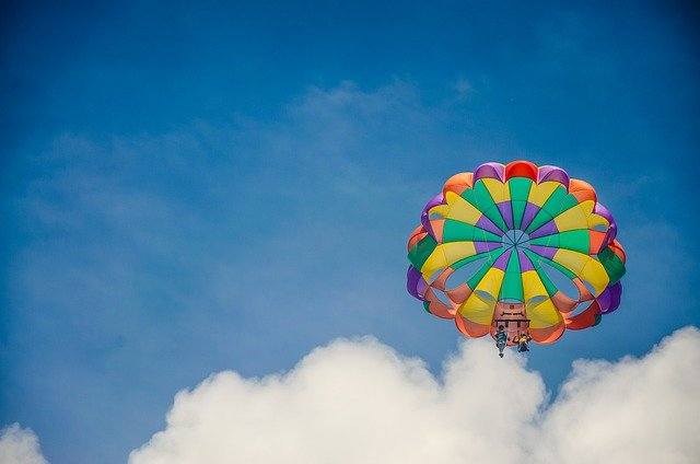 A parachute is flying through the air on a cloudy day